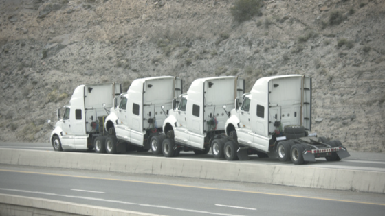 Blog Title Image of 4 white semi trucks no loads, on side of the highway.