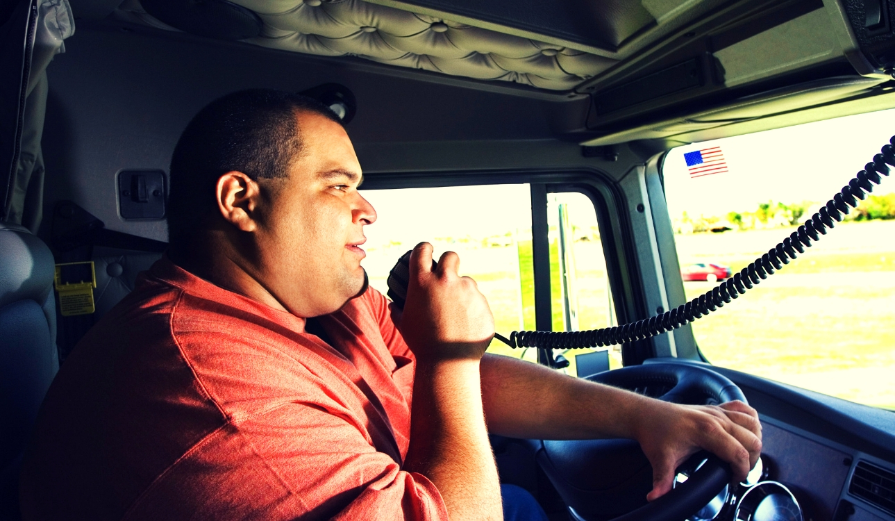 Image -Male truck driver in orange shirt speaks into his cb radio while holding a steering wheel