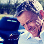 Caucasian man with short gray hair, wearing a white button up shirt, holds his neck and grimaces in front of a minor car crash