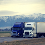 two semi trucks, 1 dark blue and 1 white drive down the highway with snow-capped mountains and farmland in the background.