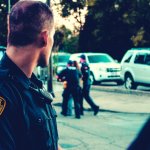 Male police officer with close cut greying dark hair in foreground looks on while 2 other police officers corral a suspect towards a fleet of white unmarked police cars in the background.