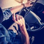Truck driver is dark blue ball cap and blue plaid shirt talks into a CB Radio