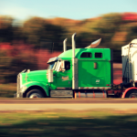 Neon Green Semi-Truck speeds past fall foliage on the highway